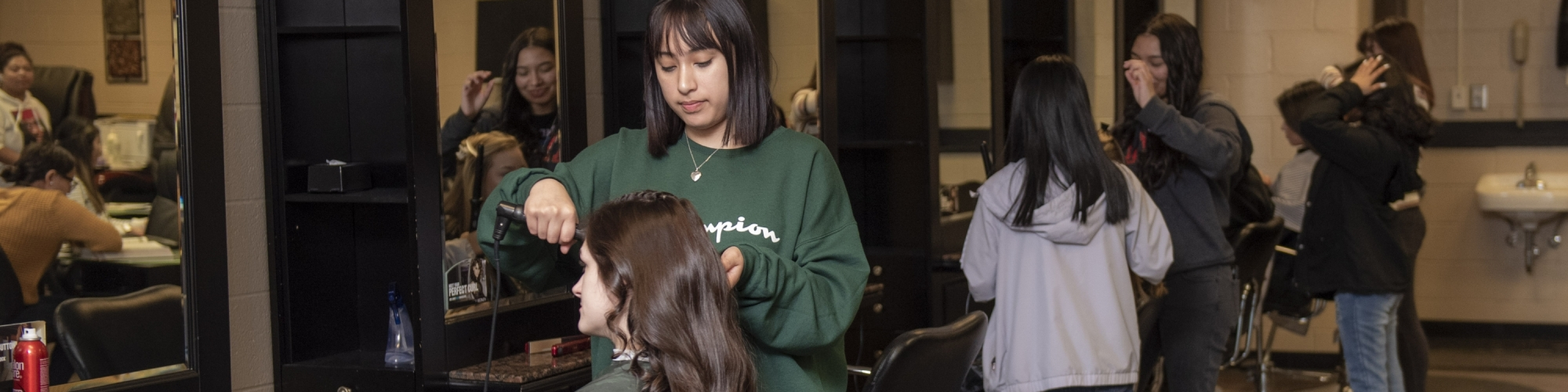 Students in Cosmetology class - curling hair